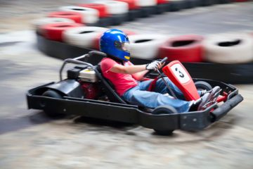 Boy in a red shirt and blue helmet is in a go kart numbered 3 similar to what they would have at the Las Vegas Mini Gran Prix