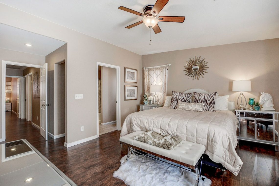 Clean booedroom, ceiling fan, dark flooring, light colored bed, freshly painted walls at 4123 HALFMOON BAY Drive Las Vegas, NV 89115