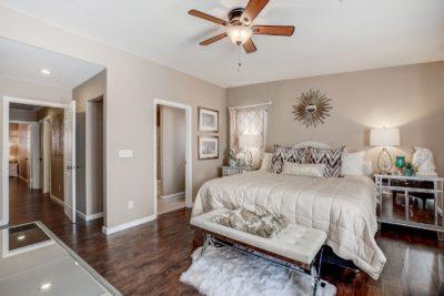 Clean booedroom, ceiling fan, dark flooring, light colored bed, freshly painted walls at 4123HALFMOON BAY Drive Las Vegas,NV89115