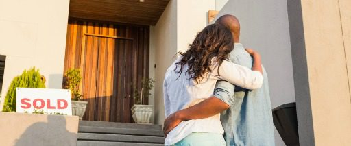 couple embracing with back to camera looking at sold home door