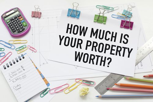 Paper, paperclicks, ruler, postcard that spells out how much is your property worth