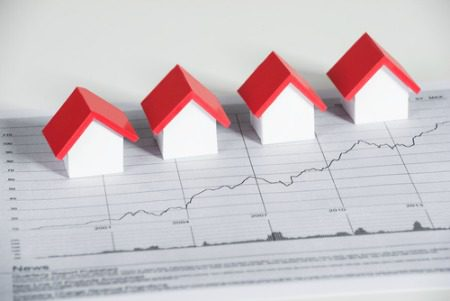 real estate market concept with graph on table and small houses sitting on graph