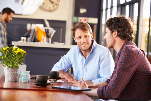 concept of two men talking over coffee about buying a Las Vegas house