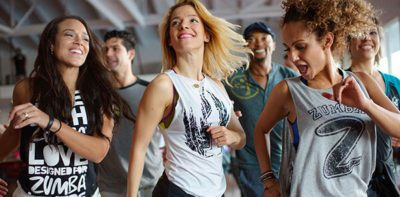 A group of people having fun while dancing in the gym