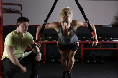 A woman is exercising while being supervised by a trainer.