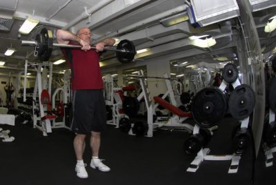 A man doing weightlifting exercise in a gym