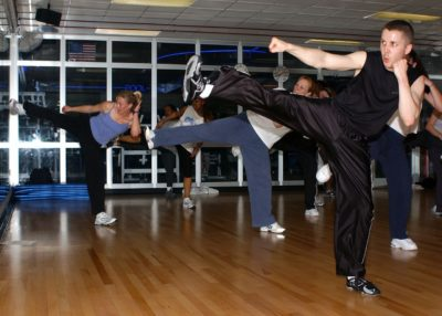 A gym full of people learning kickboxing