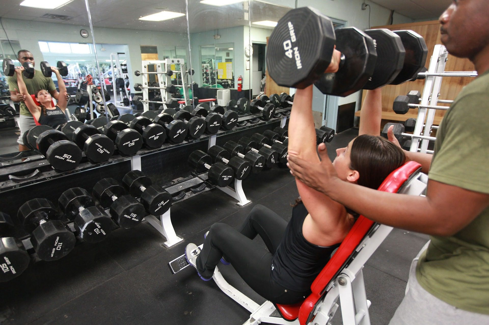 A woman lifting a heavy weight is being assisted by the trainer.