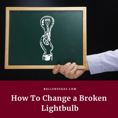 chalkboard has a light bulb drawing and is being held by a mans arm. words say how to change a broken lightbulb
