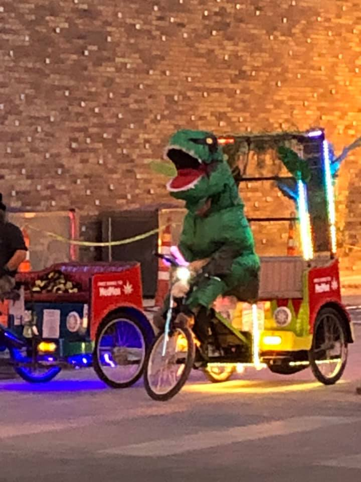 Pedi Cab driver is trying to get booked wearing a dinosaur costume.