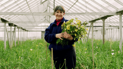 Woman is standing in a greenhouse holding flowers