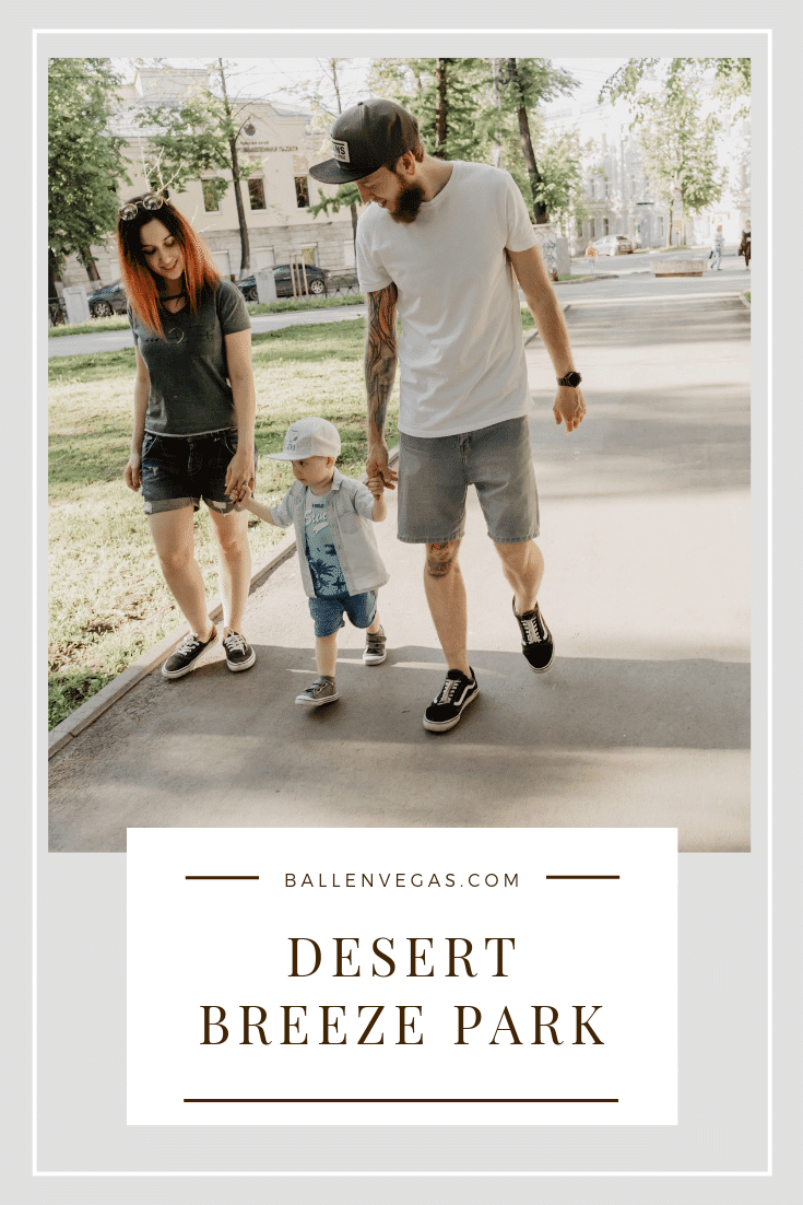A young couple is walking their child in the park and is part of the Desert Breeze Park Blog Post